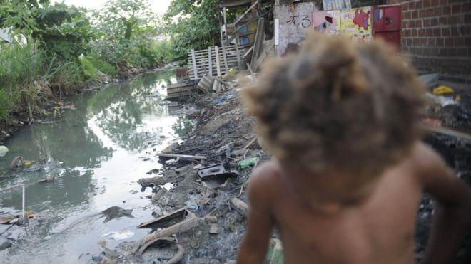 Criança ao lado de valão a céu aberto no Complexo da Maré, no Rio de Janeiro