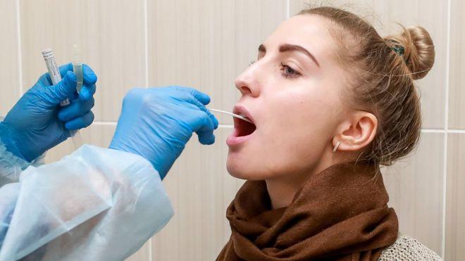 Woman having throat swab taken
