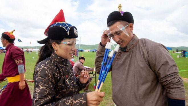 Jueces durante el festival Naadam de Mongolia, cubriéndose los rostros con pantallas protectoras, en julio de 2020.