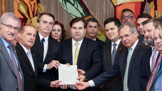 Entre outros membros do Executivo e do Legislativo, o presidente Jair Bolsonaro, o presidente da Câmara, Rodrigo Maia, e o ministro da Economia, Paulo Guedes, mostram primeiro documento com proposta da reforma