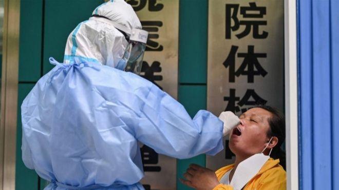 13. svibnja 2020. medicinski radnik uzima uzorak od žene kako bi testirao novi koronavirus COVID-19 u Wuhanu, središnjoj kineskoj provinciji Hubei.
