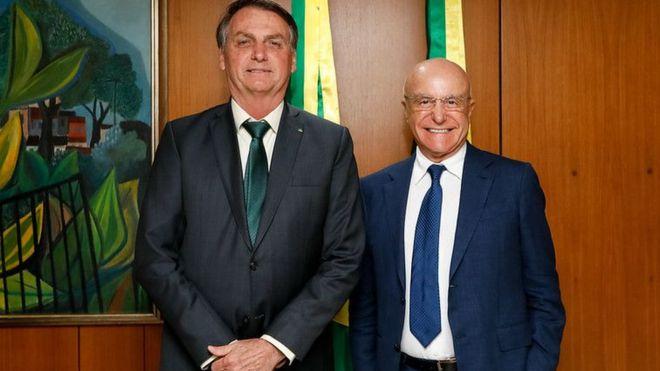 Bolsonaro e Salim Mattar posam para foto, sorrindo, de dentro de sala