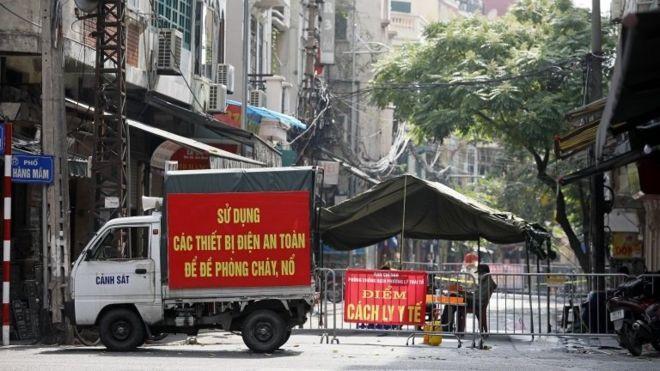 Canh gác khu vực cách ly tại một con phố ở Hà Nội, Việt Nam, ngày 19 tháng 7 năm 2021.
