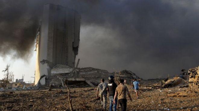 Três homens caminham em meio a fumaça e estilhaços, com prédio destruído atrás