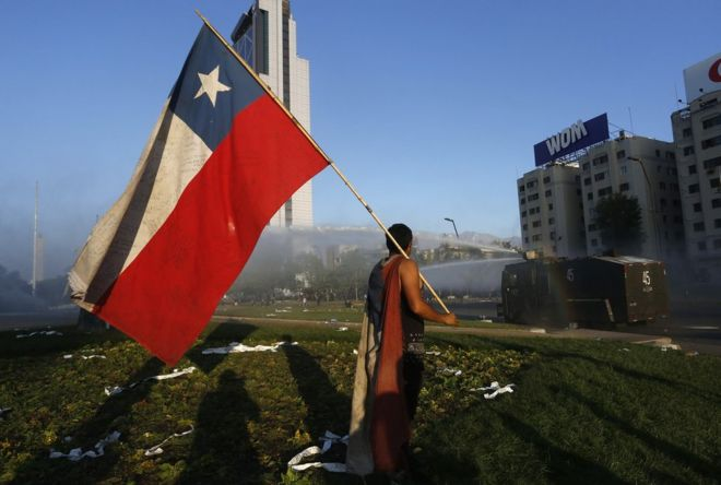 A man holds a Chilean flag in front of a tank