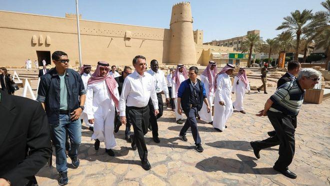 Bolsonaro em visita ao forte Masmak, em Riade, rodeado por representantes do governo saudita e assessores