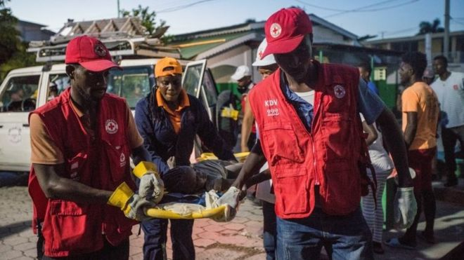 Red Cross paramedics carry a girl injured during a 7.2 magnitude earthquake in Les Cayes,
