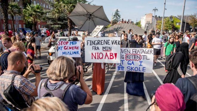 Imagem mostra mulheres segurando cartazes e sendo fotografadas em protesto realizado na cidade de Copenhague,no primeiro dia da implementação da proibição do véu no país