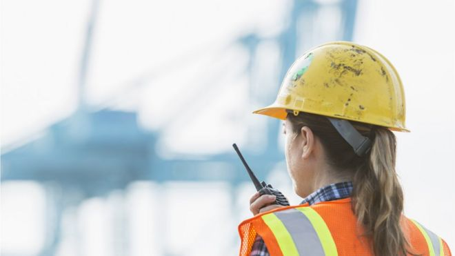 A woman wearing a hard hat and hi-visibility vest at work