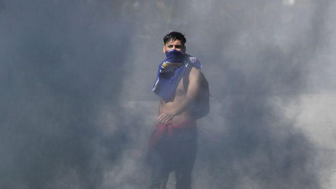 Joven emerge entre la humareda en las protestas en Chile.