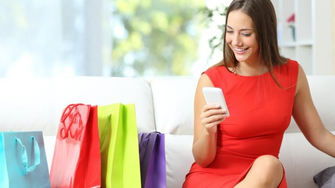 eb23ec053a60 Woman on smartphone with shopping bags