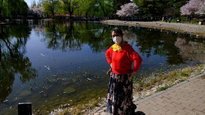 Đời sống đang dần dà trở lại bình thường tại Trung Quốc. Một phụ nữ đeo hộ khẩu ở Bắc Kinh hôm 2/4. Chính quyền nước này nói họ đã vượt đỉnh điểm của virus corona từ ngày 12/3