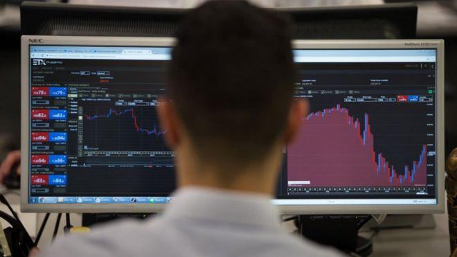 Trader looks at stock market screens
