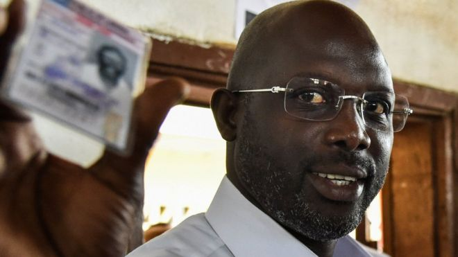 Former football star George Weah shows his voting card at a polling station in Monrovia on October 10, 2017