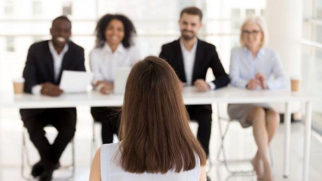 امرأة تجلس أمام هيئة تحكيم -من أصدقاء يتظاهرون بأنهم مديرين موارد بشرية- من أجل مقابلة شخصية للحصول على وظيفة