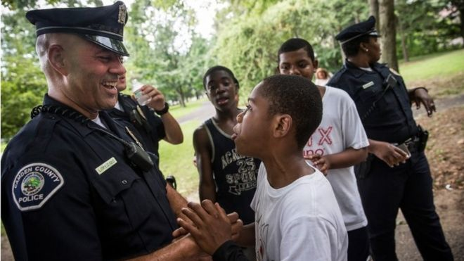 Un policía y un niño se saludan