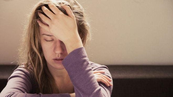 Mujer joven con dolor de cabeza.