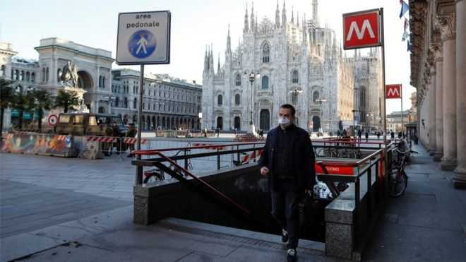 A man wearing a protective face mask walk next to a near-empty Duomo square in Milan