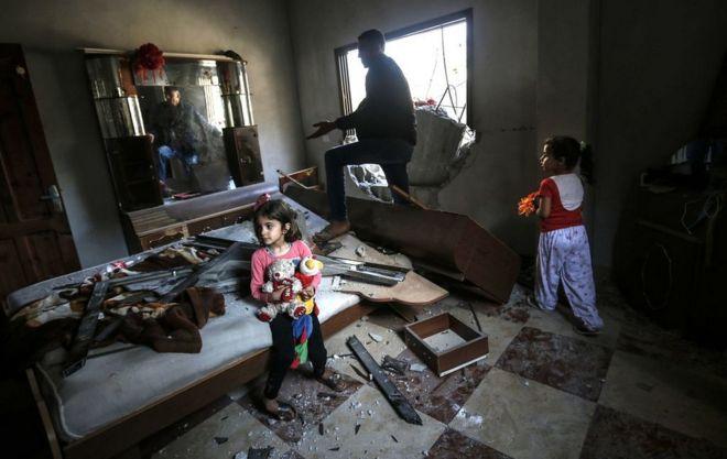 Dua bocah perempuan, yang memegang bonekanya, bersama ayahnya di ruangan tidur di rumahnya di Rafah, Gaza, tidak lama setelah Israel melakukan serangan roket ke kawasan itu, Minggu (05/05).