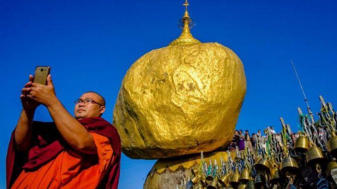 一名僧侶在緬甸大金石前自拍