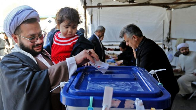 Iranians cast their ballot at a polling station in Shah Abdol-Azim Shrine, 21 February