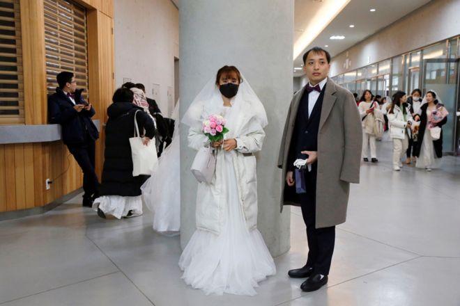 عروس ترتدي قناعاً للحماية من فيروس كورونا الجديد، تشارك في حفل زفاف جماعي أقامته الكنيسة الموحدة في مركز تشونغشيم للسلام العالمي في غابيونغ، كوريا الجنوبية.