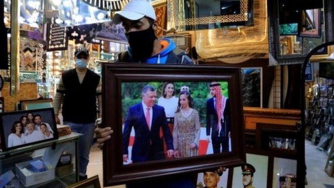 رجل يحمل صورة جماعية للعائلة المالكة الأردنية