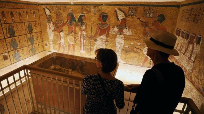 Dos visitantes frente a la tumba