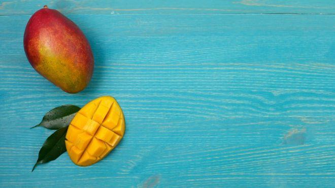 Uma manga inteira e outra cortada ao meio sobre mesa azul