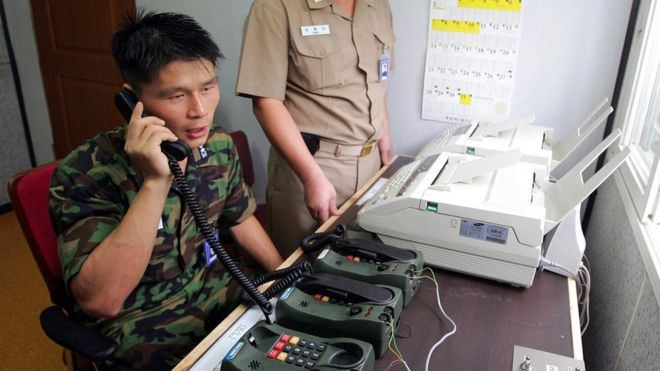 A Korean soldier on the southern side of the border speaks on a telephone, which appears to be heavy-duty and military in nature