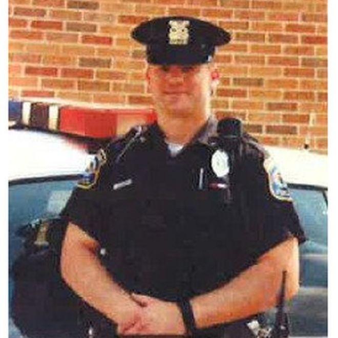 Cleo Brown, policial que se diz alvo de racismo, posa para foto com uniforme e próximo à viatura