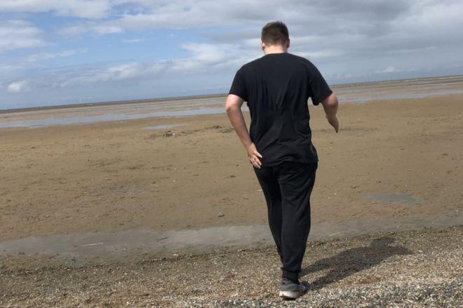 Boy walking on a beach