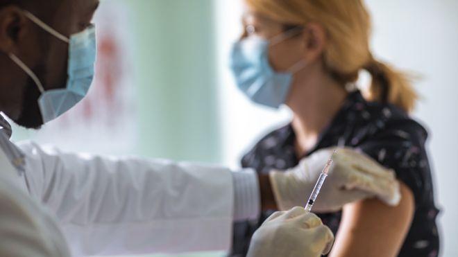 يقوم طبيب بإعطاء حقنة لشابة