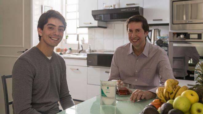 Javier e o pai sorriem, sentados à mesa da cozinha de casa