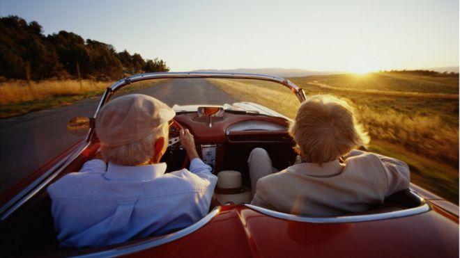 Older couple in open top car