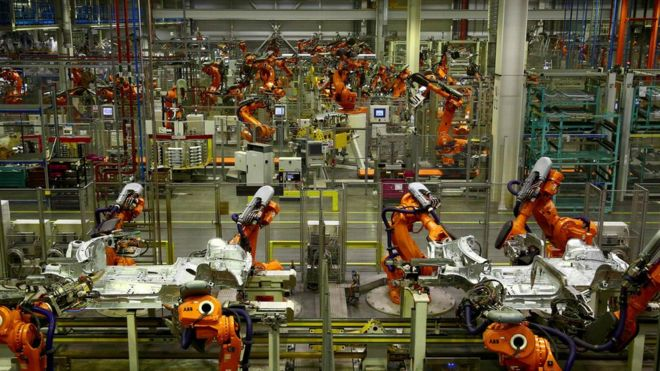 ABB robotic arms work on the body parts of Mini cars as they pass along a section of automated production line at the BMW Mini car production plant in Oxford.