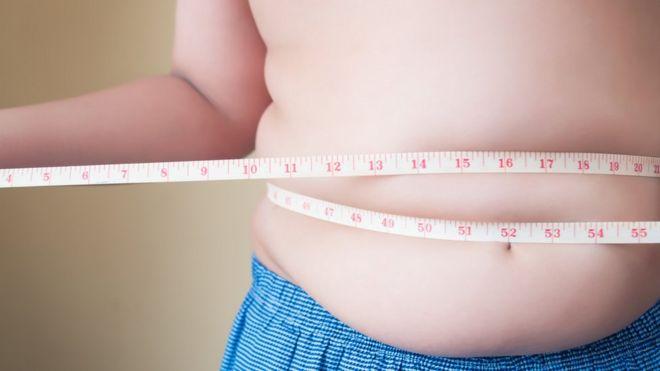Pessoa medindo a cintura com fita métrica