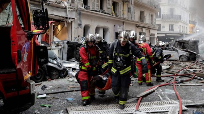 Firefighters carry an injured person after the explosion of a bakery on the corner of the streets Saint-Cecile and Rue de Trevise in central Paris on January 12, 20