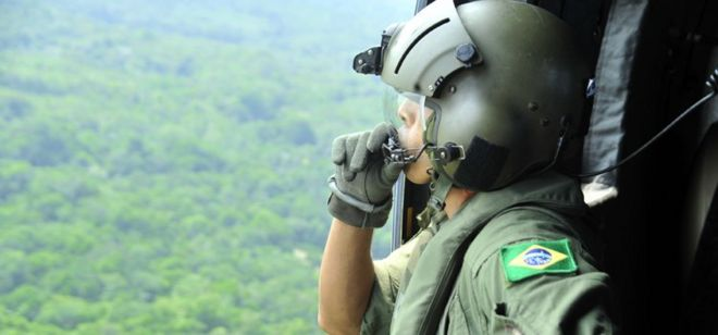 Militar olha da janela de aeronave sobre floresta na Amazônia