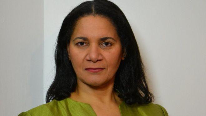 Headshot of Anne Giwa-Amu , wearing a lime green jacket