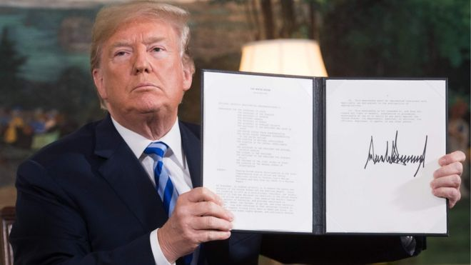 US President Donald Trump holding an order withdrawing the US from an landmark nuclear deal with Iran