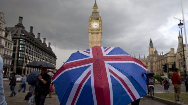 Тематический зонтик с флагом Великобритании рядом с Биг Беном у здания парламента в центре Лондона 25 июня 2016 года,