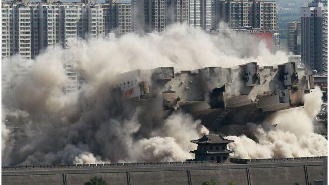 8月8日,山西大同,當地政府對位於北城牆武定西門外的一座90米高的大樓實施爆破拆除,飛揚的塵土與古城牆呼應形成壯觀場面。