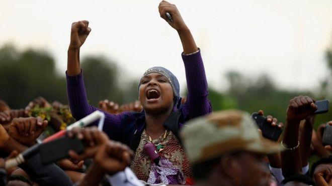 Демонстранты выкрикивают лозунги, высвечивая жест протеста оромо во время Irreecha, праздника благодарения народа оромо, в городе Бишофто, регион Оромия, Эфиопия, 2 октября 2016 г.