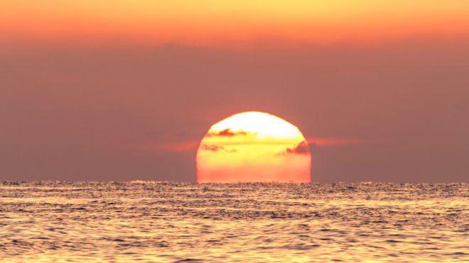 La puesta de un Sol rojo sobre el mar con el cielo color naranja