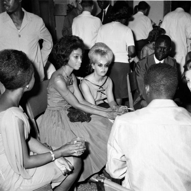 Des hommes et des femmes habillés en tenue de soirée, des boissons et des cigarettes à la main.