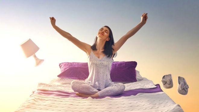 Mujer en una cama en el cielo estirando los brazos