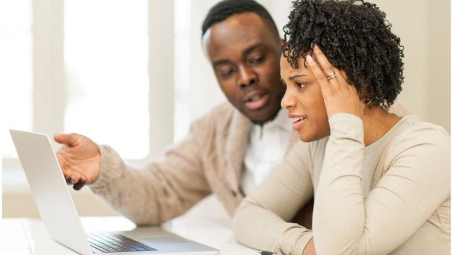 Couple discussing their financial issue in front of a laptop