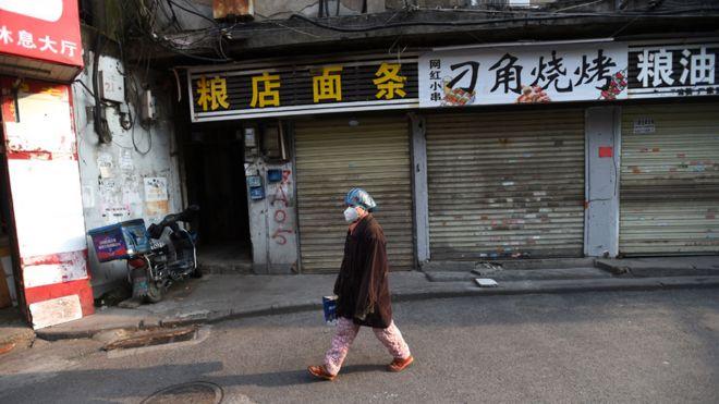 Un residente con una máscara facial y una gorra de plástico pasa por las tiendas cerradas en Wuhan, China