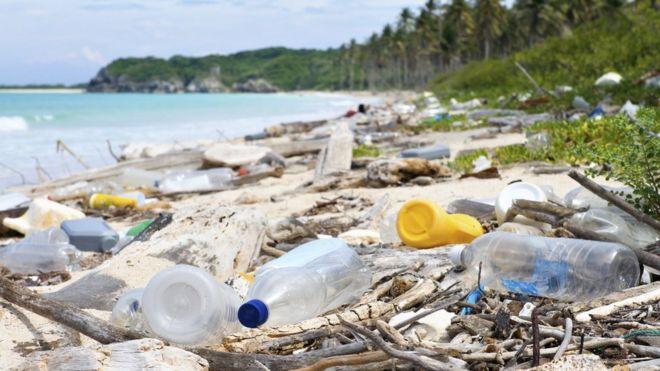 Imagem mostra lixo espalhado na areia de uma praia
